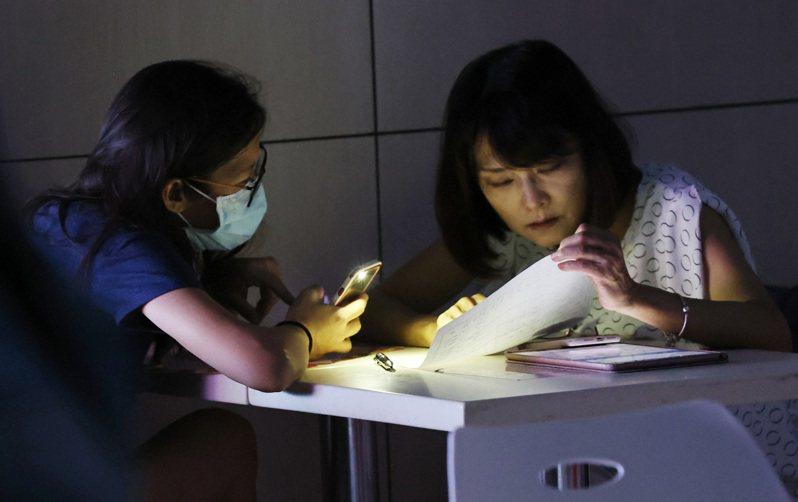 日前台電無預警停電,民眾摸黑在美食街看文件。聯合報系資料庫