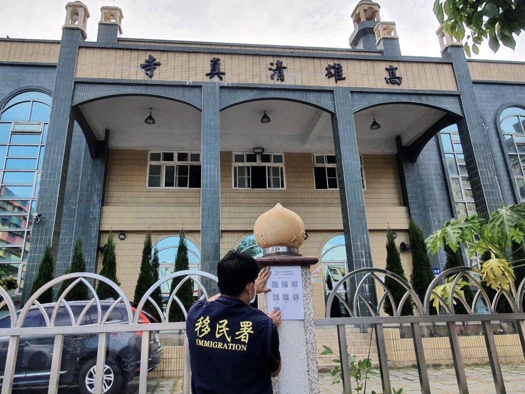 移民署人員在高雄清真寺外,張貼「安心採檢防疫專案 」 QR code 宣導傳單。...