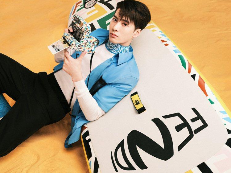 王嘉爾身穿天藍色時裝,手上拿著FF Vertigo聯名款相機。圖/FENDI提供