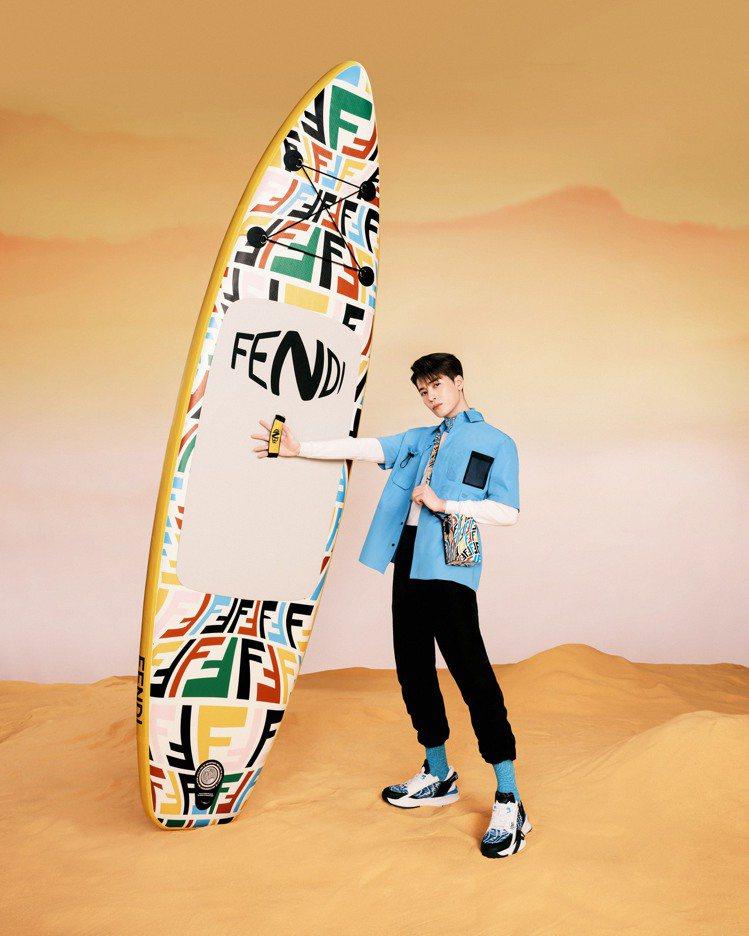王嘉爾身穿天藍色時裝,選搭FF Vertigo多色圖案的FENDI Pack包款...