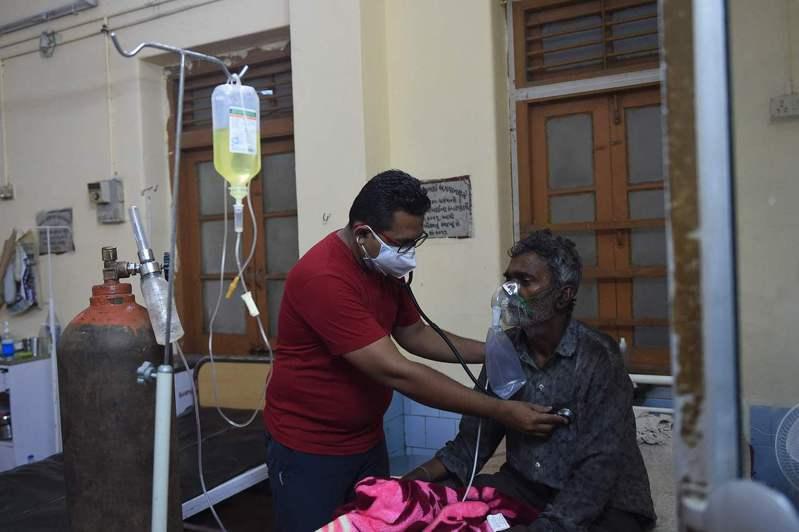 印度醫師正在檢查新冠肺炎患者。法新社
