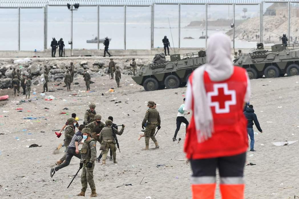 西班牙軍隊在休達海灘上,不斷與游泳登陸的上千偷渡客,爆發灘頭追逐戰。絕大部分的非...