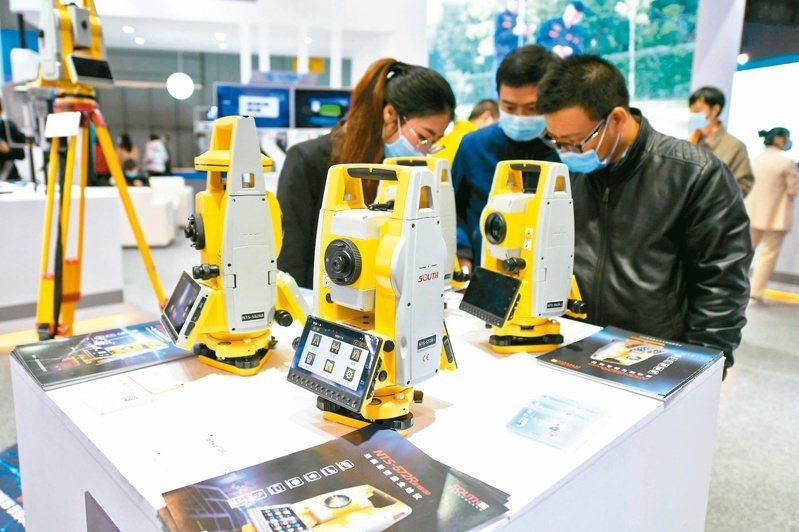 2020年底大陸「第十一屆中國衛星導航年會」,展示基於北斗衛星導航系統的最新應用與服務。圖為觀眾在展會上參觀智能全站儀產品。(新華社資料照)