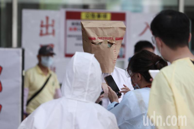 台大醫院爆工務部門10人確診,上午有醫護人員為通知醫學生考試前需普篩,以紙袋罩頭出現在醫院前。記者曾吉松/攝影