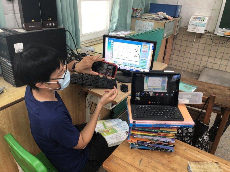 台南新化區口埤實小資訊科老師一手操作學校電腦一手操作自己的手機,解決網路卡卡問題,完成一對10名學生線上教學。圖/校方提供