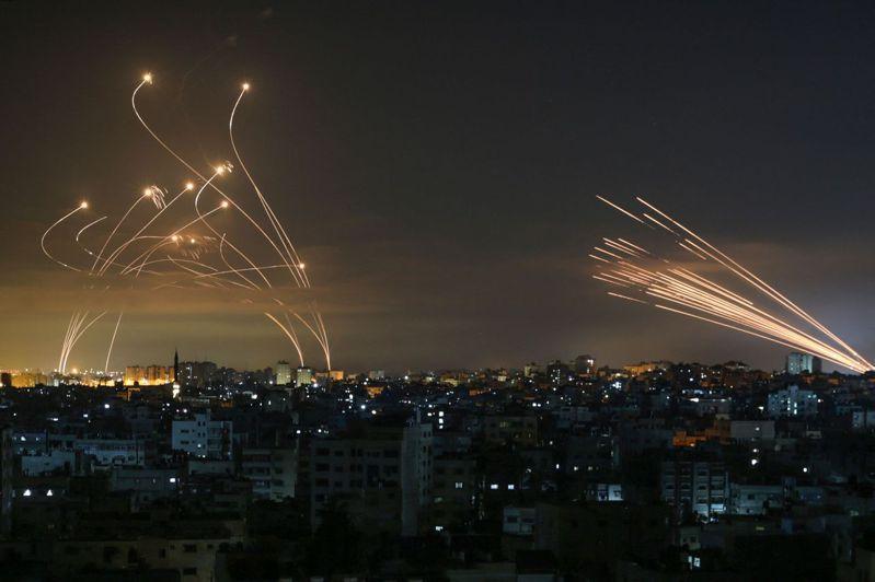 以巴衝突雙方交火激烈,哈瑪斯民兵從加薩走廊對以色列境內發射火箭(右測),以色列鐵穹飛彈空中大轉彎迎戰火箭彷彿科幻場景。法新社