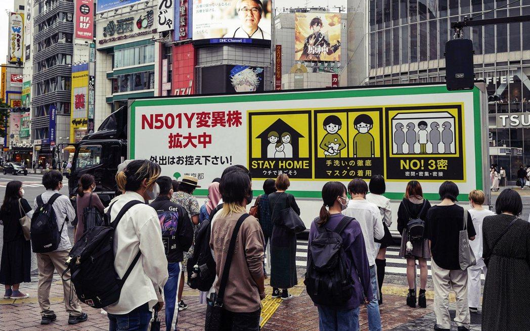 圖/歐新社:東京街頭的防疫宣導,不過外出人流依然眾多。