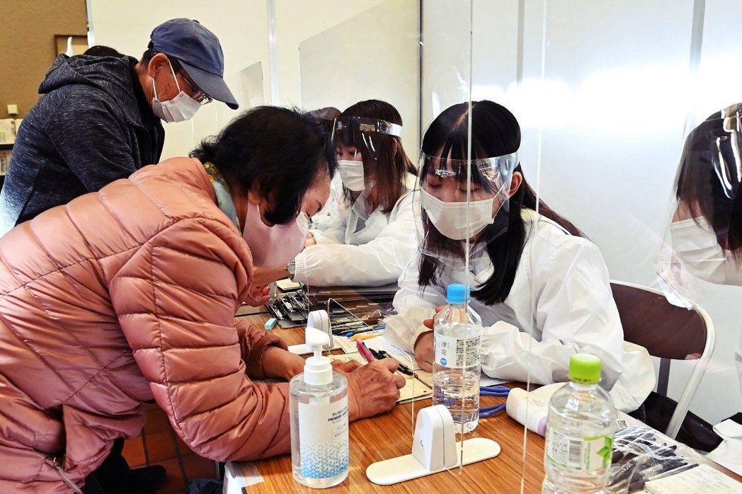 圖/法新社:開設在東京八王子飯店的疫苗接種登記。不過現階段開放的線上預約,目前...