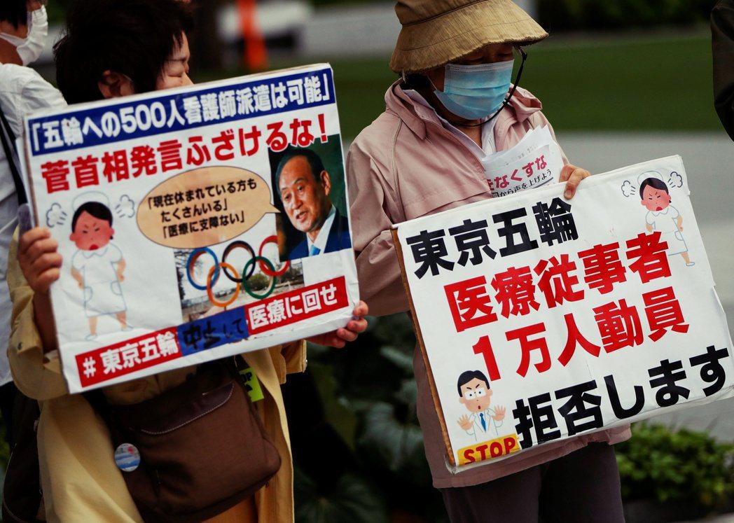 圖/路透社:圖為反東京奧運的民眾高舉標語:拒絕動員1萬名醫療工作者。先前有醫護人...