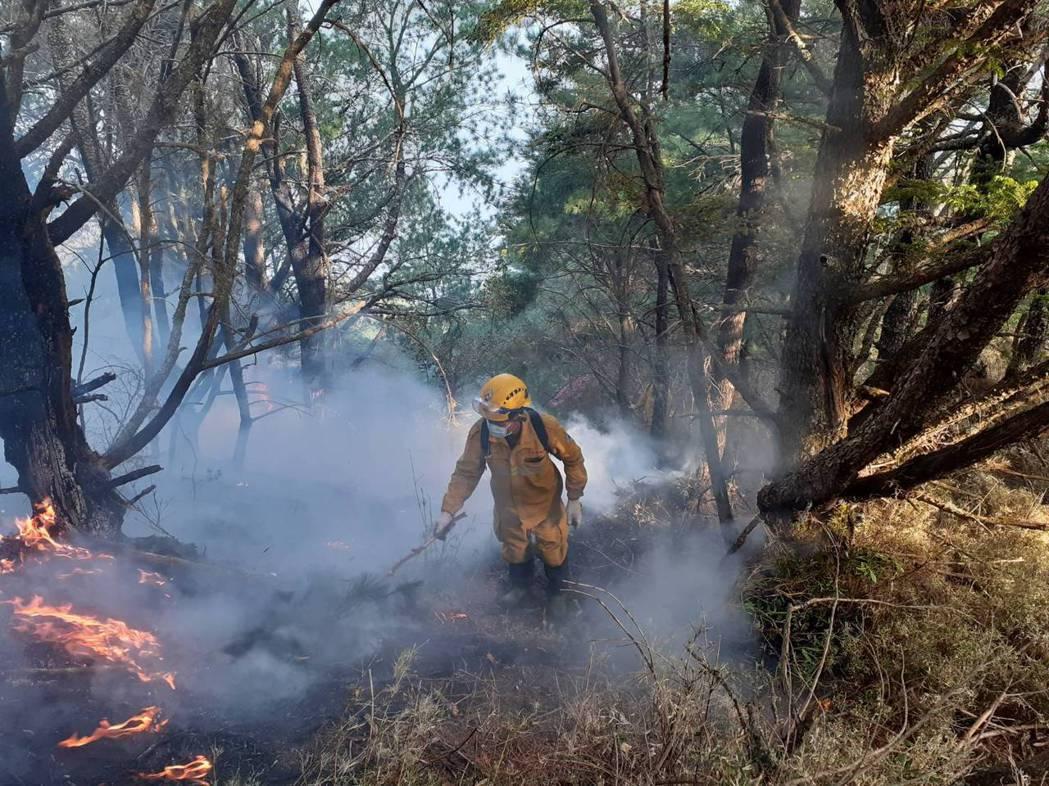 杜鵑營地大火邁入第100小時,火勢仍持續延燒超過52公頃,林管處護管員持水袋進入...