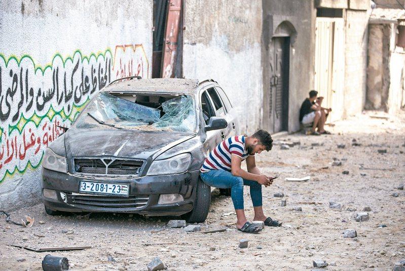 加薩走廊經過以色列猛烈空襲後一片狼藉,一名巴勒斯坦男子廿日坐在被炸毀的汽車上發呆。(美聯社)