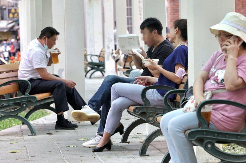 由於許多餐飲業者配合防疫都取消內用,僅限外帶,不少民眾外帶食物後,轉往到公園用餐。 記者林俊良/攝影
