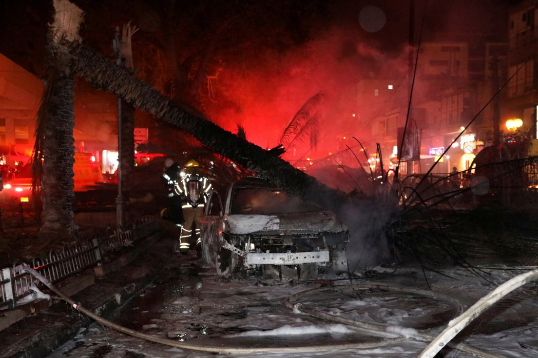 圖為5月11日,一名消防員路過一處遭火箭彈擊中、起火的汽車。 圖/路透社
