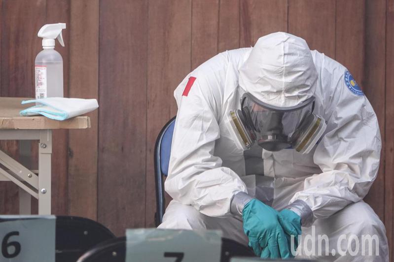 台灣疫情持續擴大,連續7天本土確診人數破百例。圖為篩檢人員在一旁待命準備。記者葉信菉/攝影