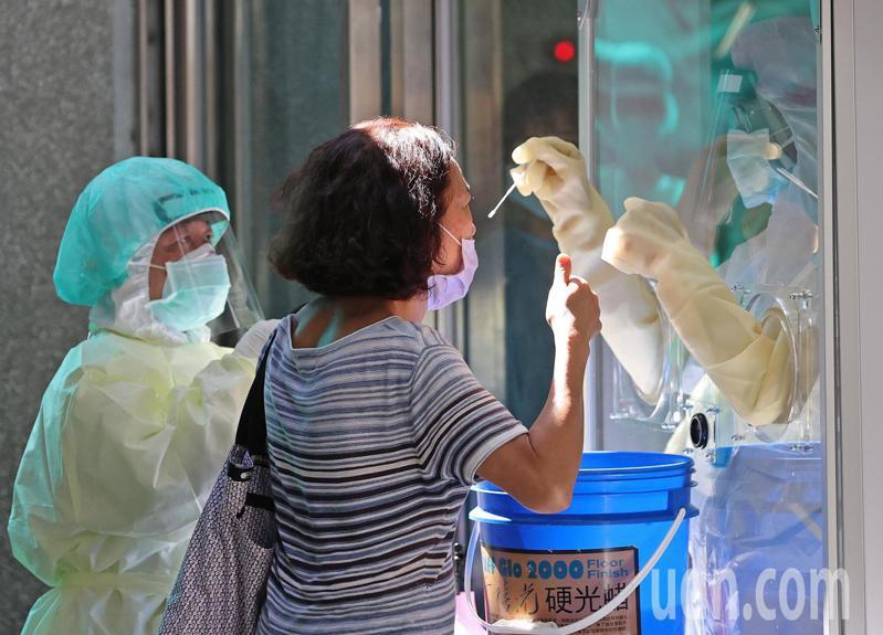 新冠肺炎嚴峻,新北市中和社區篩檢站今天首度設在市民活動中心,醫護人員隔著玻璃逐一採檢,受檢民眾豎起拇指稱讚謝謝醫護人員的幫忙。記者潘俊宏/攝影