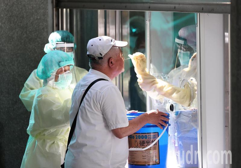 新冠肺炎疫情嚴峻,圖為醫護人員隔著玻璃為民眾採檢。記者潘俊宏/攝影