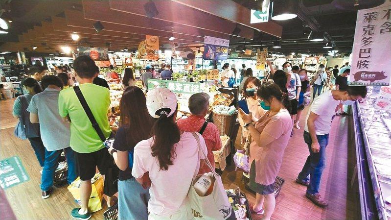 疫情緊繃,大批消費者湧入量販超市搶買防疫用品與民生物資。圖/報系資料照片