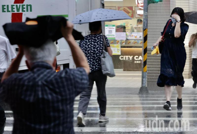 台北市傍晚時分下了一場陣雨,不少未帶傘的市民淋雨前行,而這場雨為水泥都市降溫不少,也對近來吃緊的電力供應有所幫助。記者許正宏/攝影