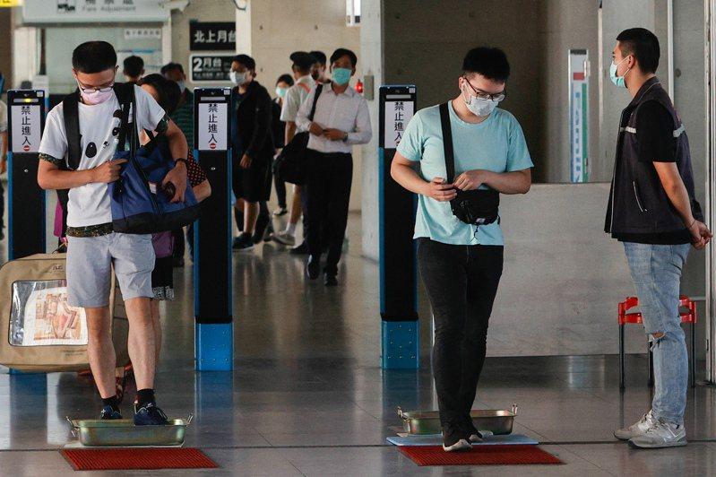 國內疫情升溫,台鐵台中站出站民眾,必須走過裝有消毒水的集水盆後,才能出站。記者黃仲裕/攝影