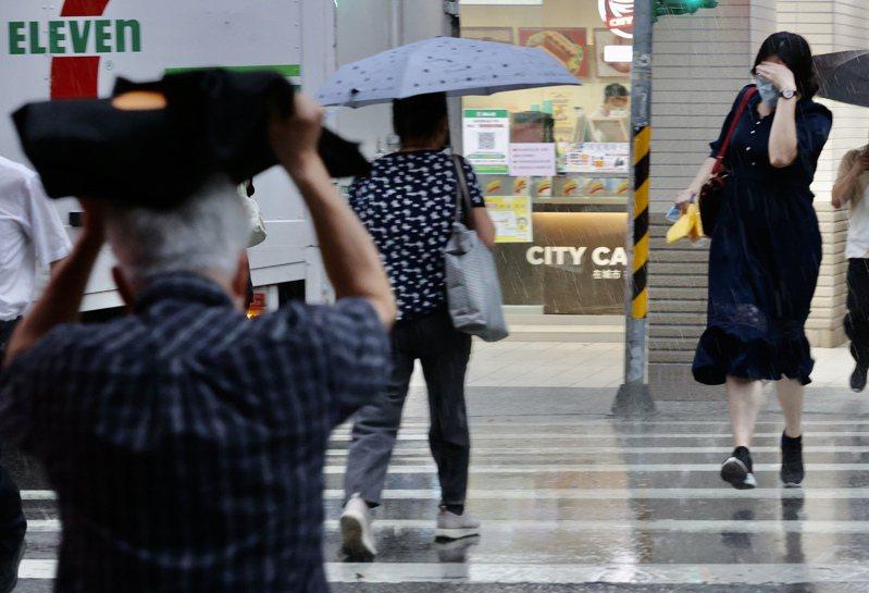 台北市昨日傍晚時分下了一場陣雨,不少未帶傘的市民淋雨前行。記者許正宏/攝影