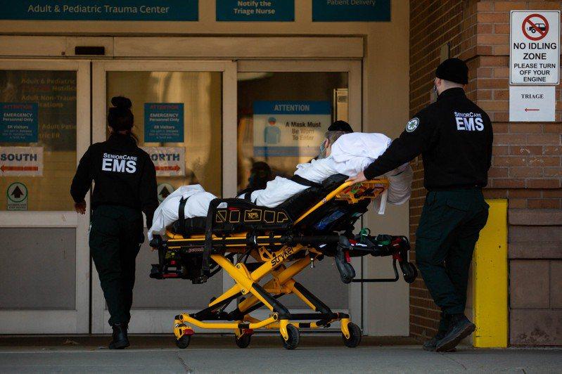 圖為日前美國紐約的醫護人員在醫院外運送病人。新華社