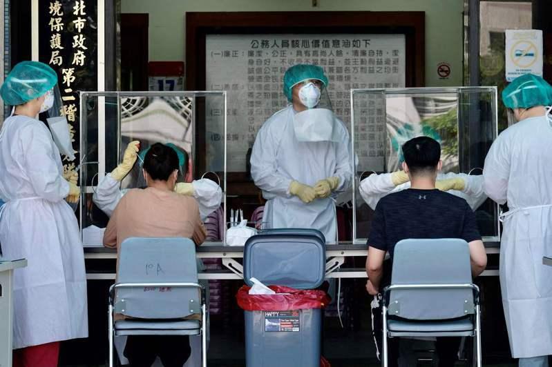台灣新北市新店區醫護人員廿一日正為當地居民進行病毒檢測。(法新社)