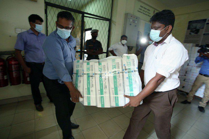 斯里蘭卡工人三月卅一日在首都可倫坡班達拉奈克國際機場搬運國藥疫苗。新華社