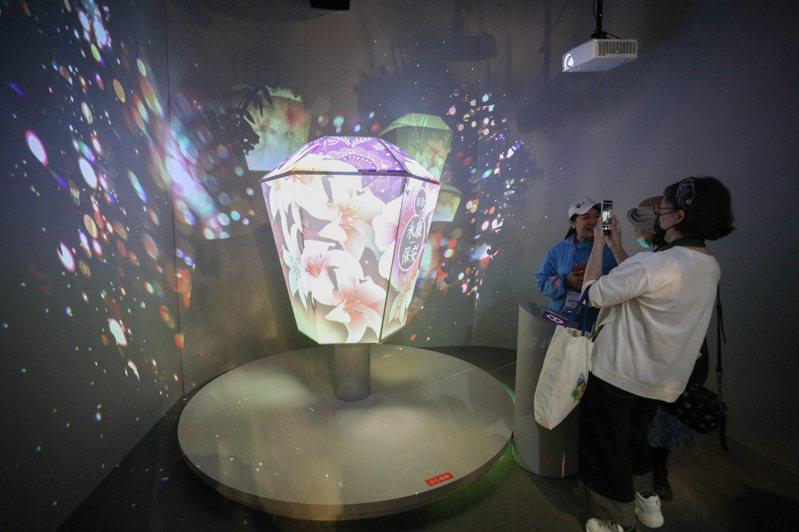 「第十屆中國花卉博覽會」台灣室內展區、室外展園,22日以視訊連線方式剪綵開園。圖為遊客感受天燈藝術裝置的奇妙光影。(中新社)