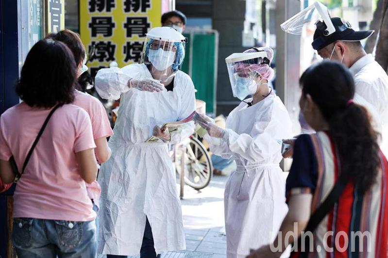 近一周每日本土新增確診案例均破百件。圖為穿戴全副防護裝備的西園醫院醫護人員,向排隊領篩檢號碼牌的民眾說明到院時間及注意事項。記者侯永全/攝影
