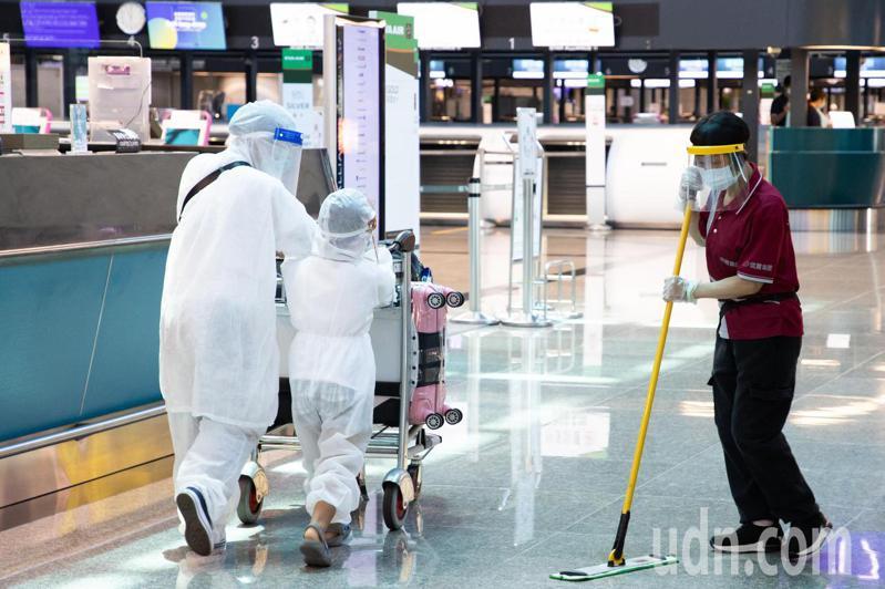 桃園機場今天上午11點再度進行深度大清消,今天深度清消的重點放在旅客和民眾直接觸摸到的物件上面,一對母子穿著全身防護衣準備前往報到櫃檯報到。記者季相儒/攝影