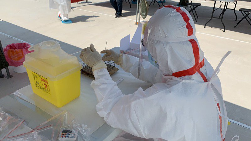 第一線醫護人員穿著隔離衣忙著採檢。記者陳苡葳/攝影