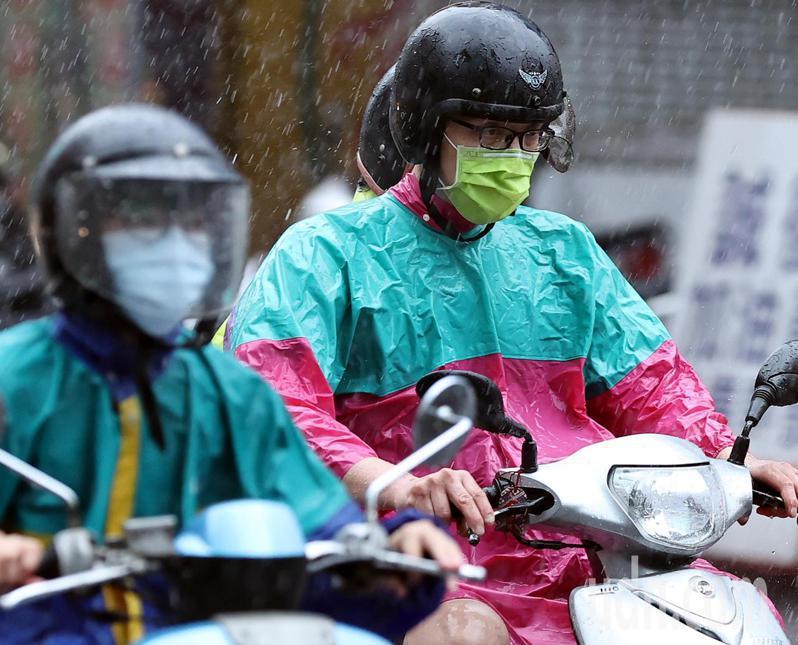 有些機車族因安全帽透明面罩有礙視線,將面罩摘除,不過雨中騎車口罩卻遭大雨淋濕,溼答答的口罩勢必影響呼吸順暢。記者侯永全/攝影