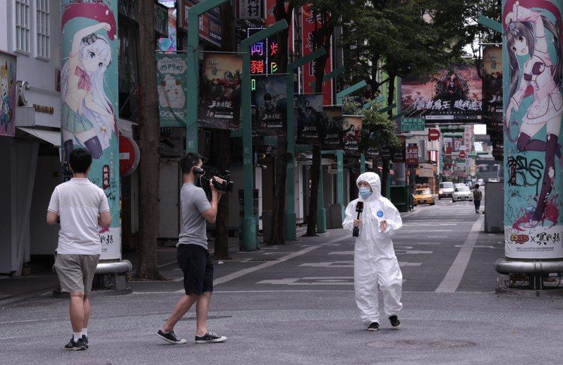 空曠的西門町媒體記者配戴口罩外,還加戴護目鏡與全身的防護衣,來確保自身的安全,而負責攝影的人員只著短身、短褲,難免讓人為他們「捏一把冷汗」。記者黃義書/攝影