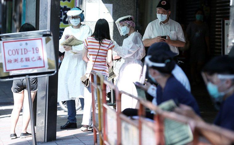 民眾在西園醫院人行道排隊領號碼牌,等候篩檢。記者侯永全/攝影