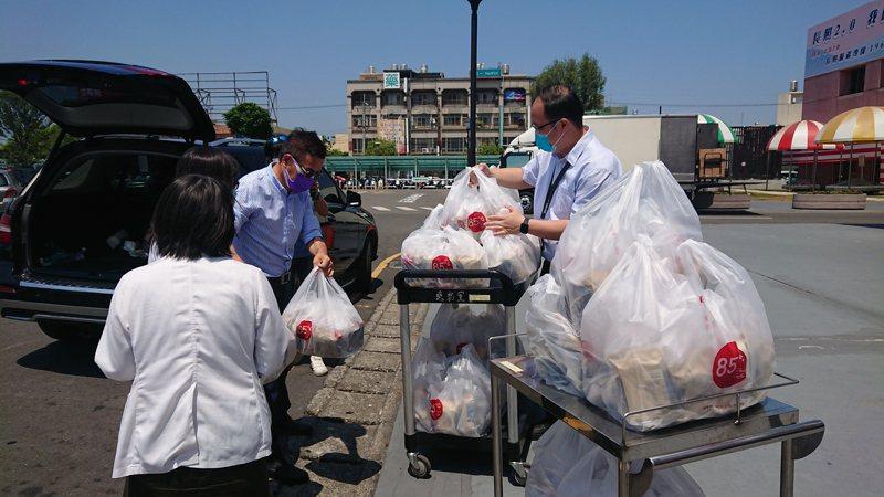 彰化縣埔心社區發展協會理事長許增鏞(左)一連五天捐200份咖啡和蛋捲給彰化醫院,行政人員推車出來拿取。記者簡慧珍/攝影