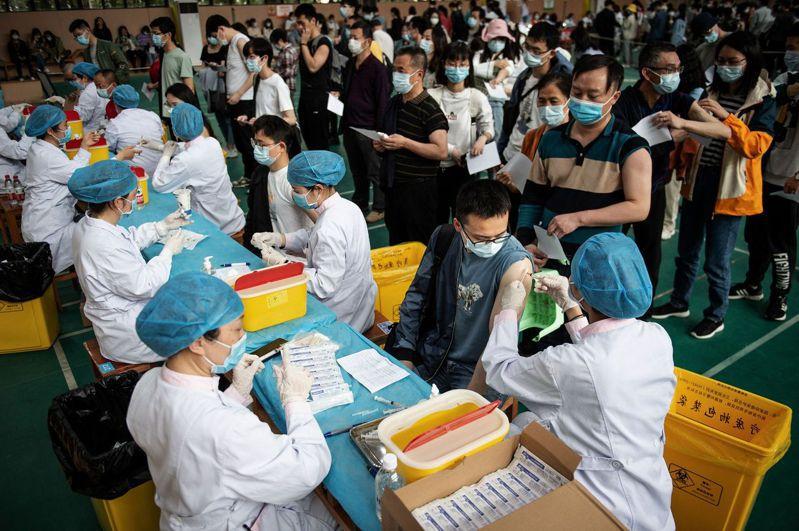 新冠病毒已在全球造成347萬多人死亡。圖為武漢一所大學上月28日給學生接種中國生物技術公司研發的新冠疫苗。法新社