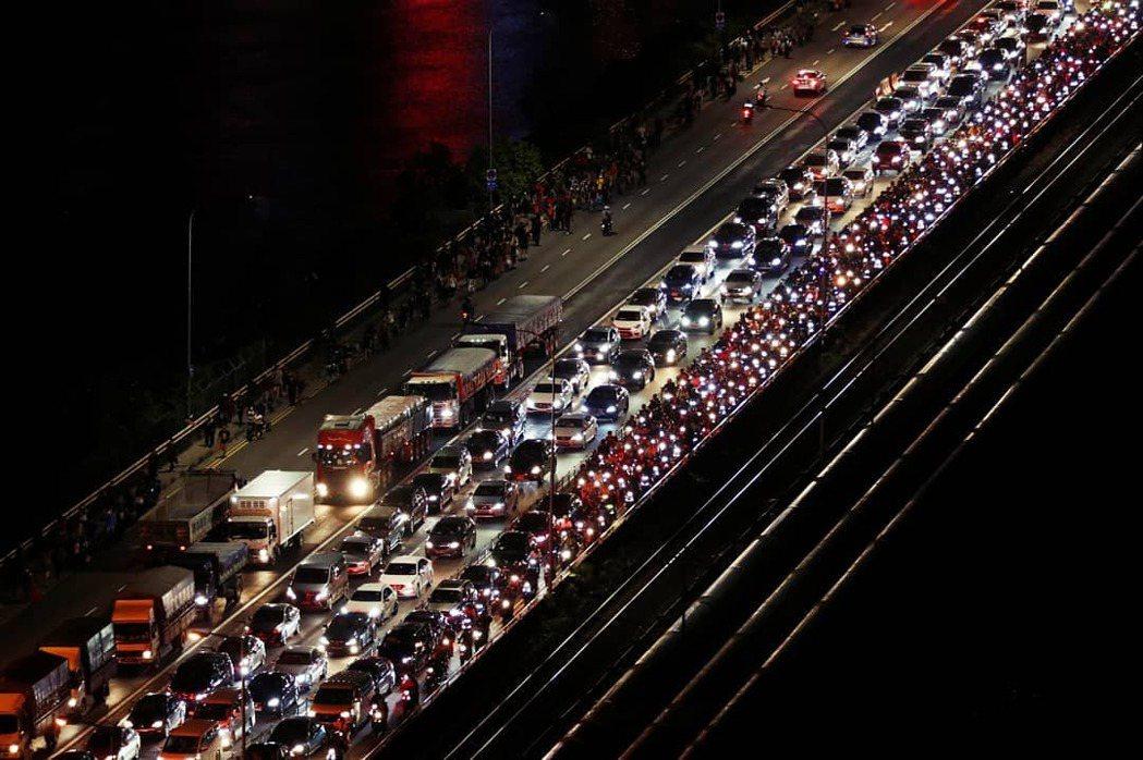 圖為去年三月馬來西亞宣布封關之際,當時塞車又塞人的新柔長堤。 圖/路透社