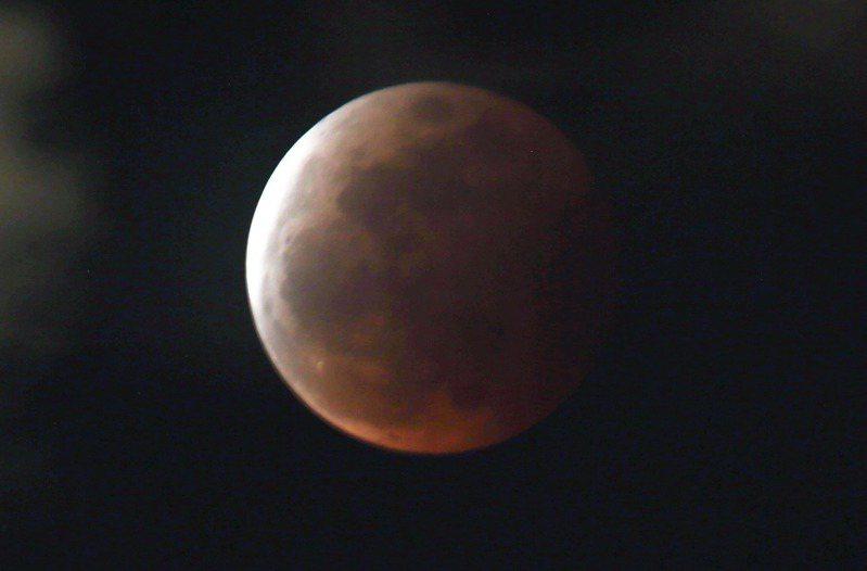 台灣地區晚上出現月全食現象,高雄壽山頂可見夕陽西下後月全食現身,紅色月亮搭配地景讓民眾驚呼。記者劉學聖/攝影