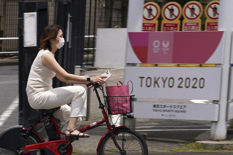 東京疫情燒 東京街頭一名女子廿六日戴口罩騎車經過東奧與帕奧的宣傳旗幟。(美聯社)