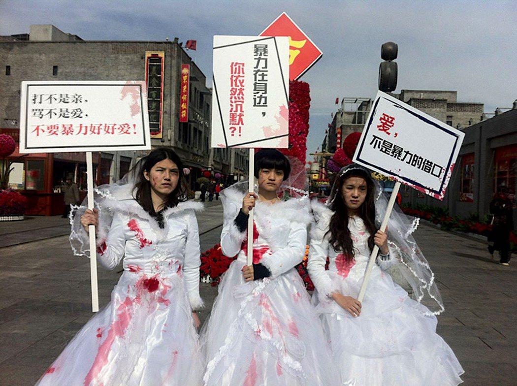 圖為2012年,肖美麗(中)與女權行動派組織了「帶血的婚紗」,傳達反家庭暴力的訴...