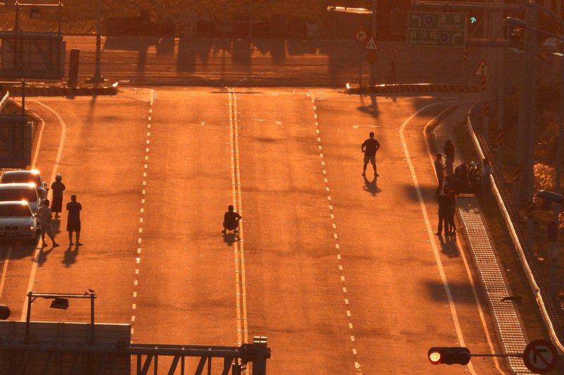台61線新埔交流道落日大道最近因日落方向逐漸對正大道,吸引攝影愛好者及駕駛人停留駐足,但出現車輛違停、行人任意穿越車道的亂象。圖/民眾提供