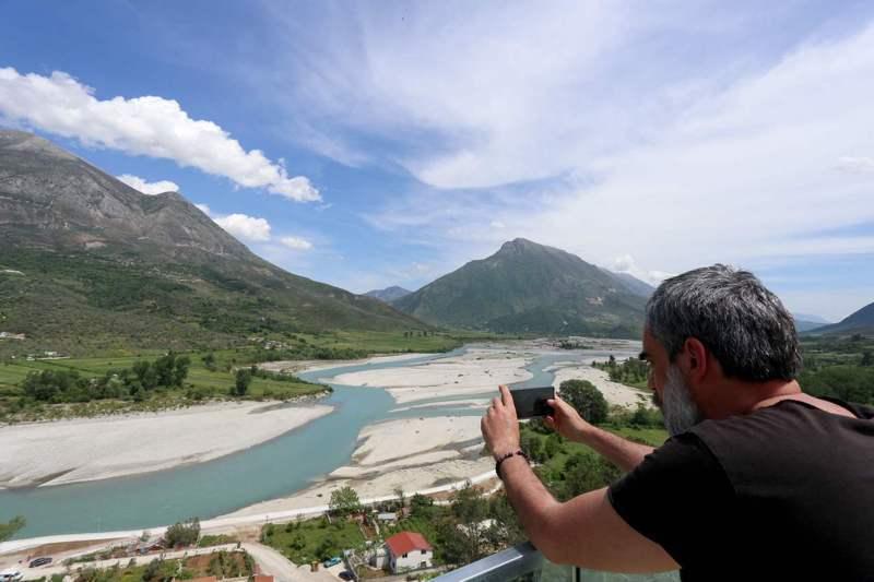 一名旅客用手機拍下維約薩河風光。法新社