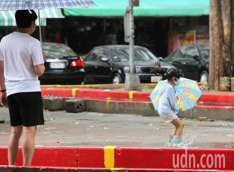高雄地區下午兩點左右下雨了,民眾開心不已,還有小朋友拿著雨傘到外頭開心淋雨。記者劉學聖/攝影