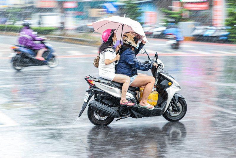 梅雨鋒面逐漸抵台,上午北部出現雨勢,有來不及穿上雨衣的機車騎士,靠著後座撐傘擋
