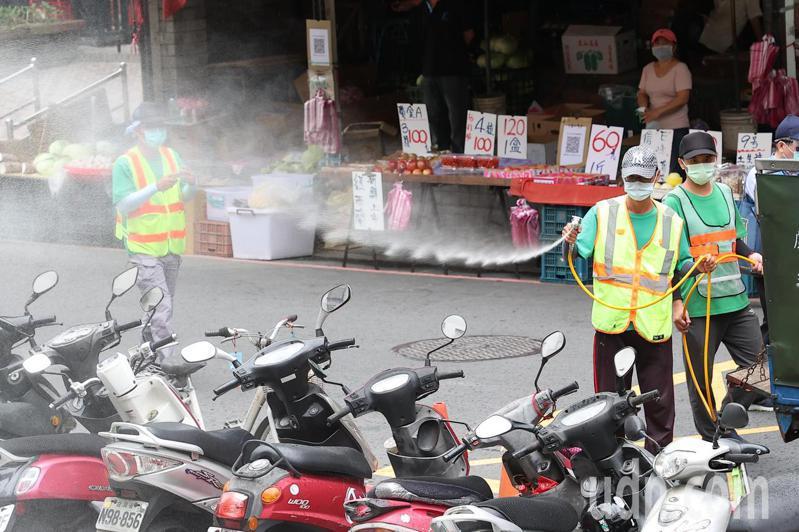 菜市場內有人員隨時對環境進行消毒。記者葉信菉/攝影