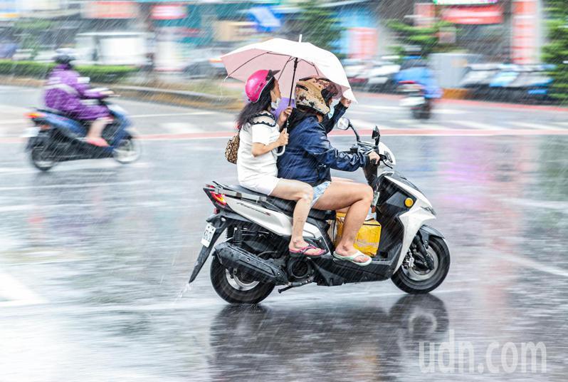 梅雨鋒面逐漸抵台,上午北部已有降雨,有來不及穿上雨衣的機車騎士,靠著後座撐傘抵擋大雨。記者曾原信/攝影