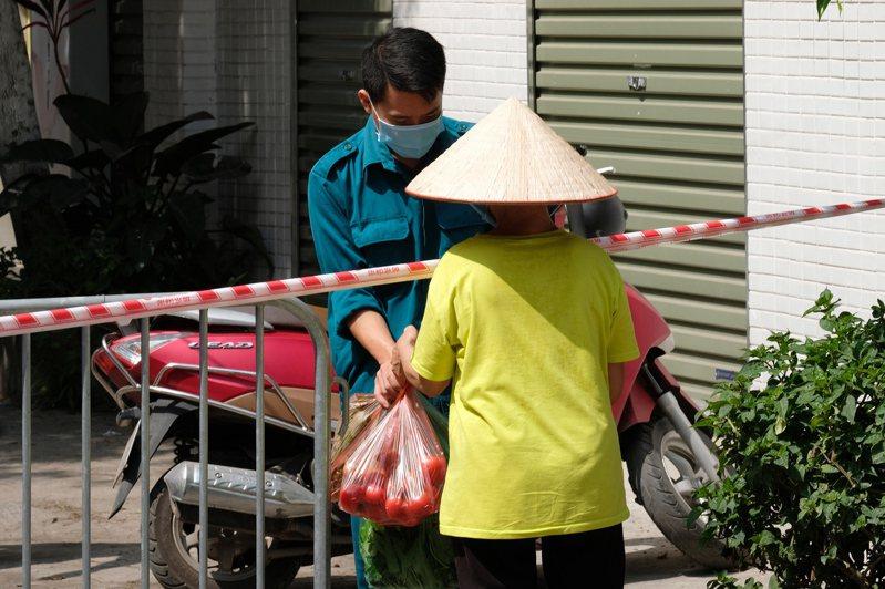 越南首都河內一名男子26日在封鎖區內領取食物。(歐新社)