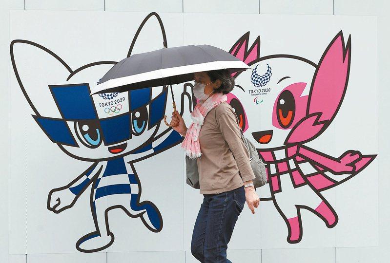 東京一名戴口罩的女子廿八日行經繪有東奧和帕奧吉祥物的牆壁旁。(路透)