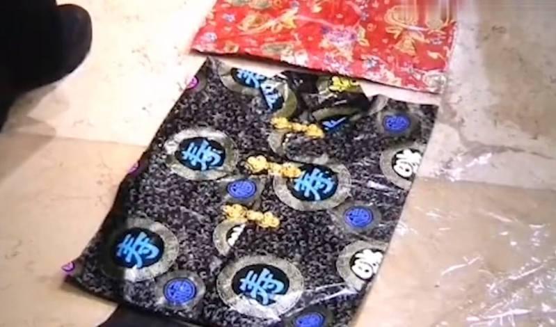 中國有女子在淘寶網購買藥膏後,留了負評,竟收到1個不明來歷的包裹,一拆開發現是2套壽衣。 圖/影片截圖