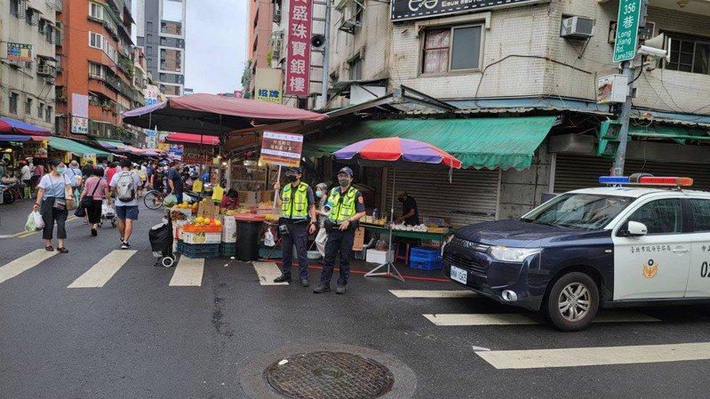 為防堵傳統市場湧人潮成防疫破口,台北市警方30日派遣警力到場,以手持看板、防疫廣播等方式於市場出入口進行宣導防疫和人流管控。(台北市警察局中山分局提供) 中央社